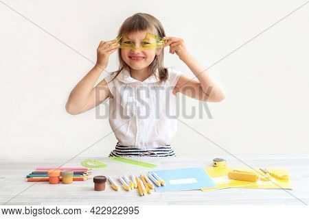 The Concept Of Doing Homework. Cheerful Eight-year-old With Rulers In Her Hands Sits At The Table, D