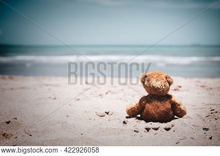 Alone Toy Teddy Bear Doll Sitting On Sand Beach With Blue Sea. Lonely, Sad, Broken Heart Or Internat