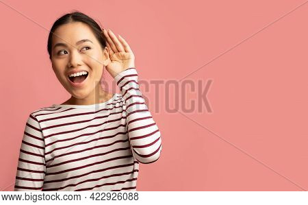 Curious Cheerful Asian Woman Keeping Hand Near Ear Trying To Overhear Something