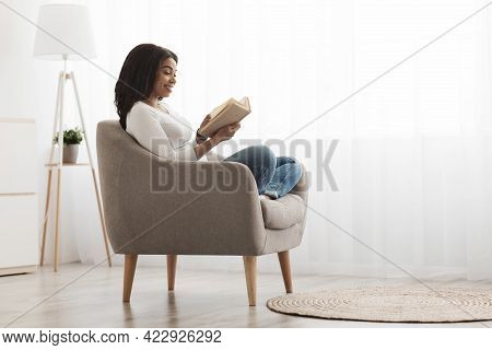 Weekend Pastime. Relaxed African American Woman Reading Book In Comfortable Armchair Against Window,