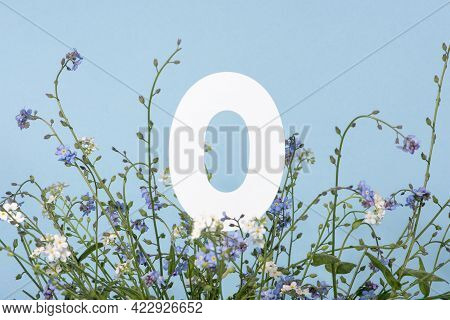Number Zero Among Blue Flowers On Blue Background. Birthday, Anniversary, Jubilee Concept. For Invit