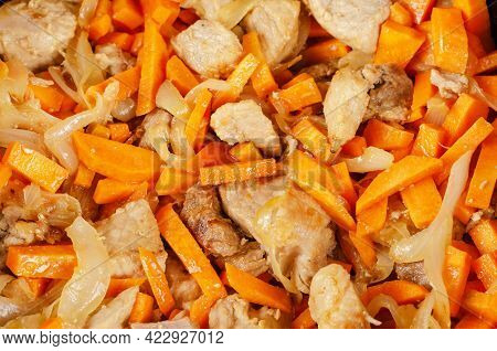 Meat With Vegetables In The Cauldron. Pork Chunks Mixed With Onions And Carrots. Cooking Pilaf. Home