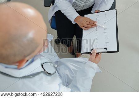 Cardiologists Discussing Cardiogram Of Patient With Dangerious Disease, View From Above