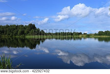 Beautiful Summer Sunny Landscape With A Calm Big River, Trees And Wooded Banks On The Other Side. Bl