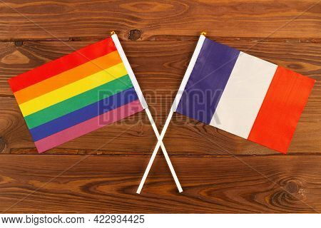 Rainbow Flag Lgbt And Flag Of France On Brown Wood Planks Background. Lgbt Pride Month. Lgbtq. Lgbtq