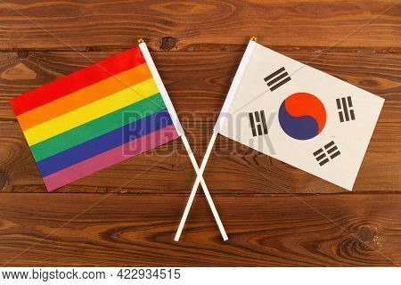 Rainbow Flag Lgbt And Flag Of South Korea On Brown Wood Planks Background. Lgbt Pride Month. Lgbtq.