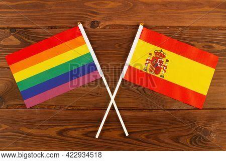 Rainbow Flag Lgbt And Flag Of Spain On Brown Wood Planks Background. Lgbt Pride Month. Lgbtq. Lgbtqi