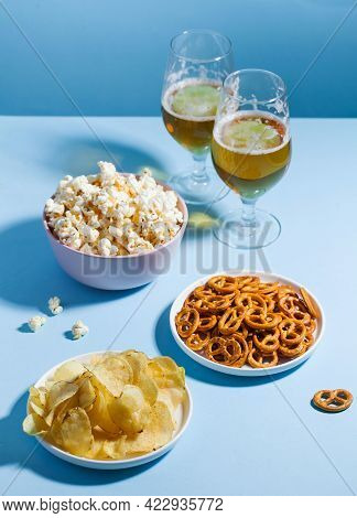 An Assortment Of Unhealthy Snacks, Such As Chips, Popcorn, Pretzels, In Bowls And Glasses With Light