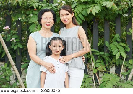 Three Generation Of One Family: Grandmother, Mother And Daughter Standing Outdoors
