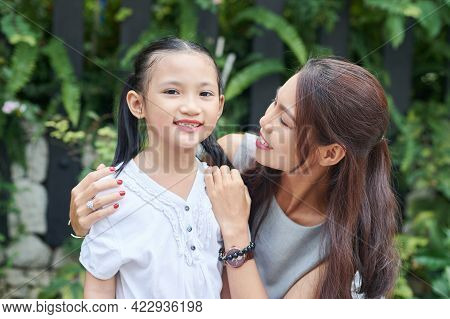 Happy Young Woman Looking At Her Preteen Daughter Standing Outdoors And Smiling At Camera