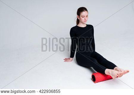 A Beautiful Girl Trainer In A Black Sweater And Leggings Sits On The Floor And Does An Exercise Usin