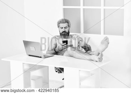 Self Quarantine Routine. Serene Barefoot Guy Resting, Remote Workday With Computer. Networking While