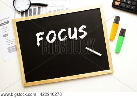 Text Focus Written In Chalk On A Slate Board. Office Desk With Office Supplies. Business Concept.