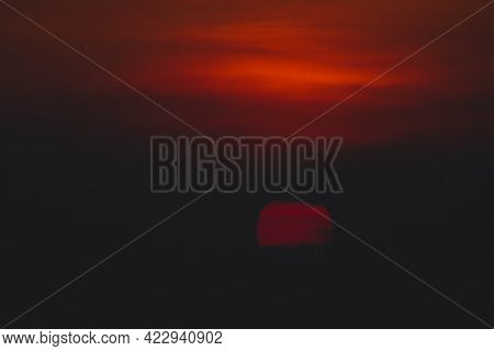 Beautiful Sunset. Dramatic Fiery Sun Surrounded By Clouds During Sunset.  Vibrant Orange Red Clouds