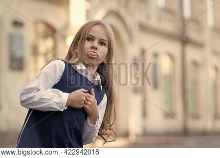 Childhood Is Full Of Learning. Funny Child Stick Out Tongue. Little Girl Wear Uniform Outdoors. Back