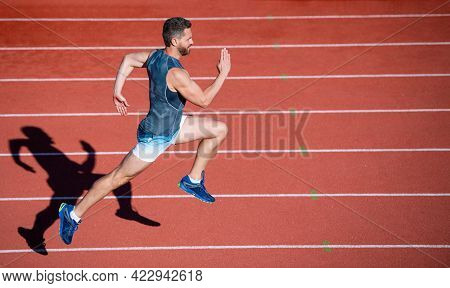 Energetic Athletic Muscular Man Runner Running On Racetrack At Outdoor Stadium, Hurry Up