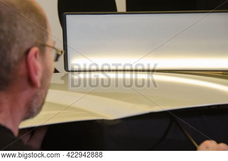 Professional Paintless Dent Repair Technician Is Repairing Dents On Car Body. Man Removing Dent On C