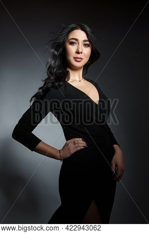 Beautiful Brunette Woman In A Black Dress Poses In The Studio. Elegant Girl With Beautiful Natural M