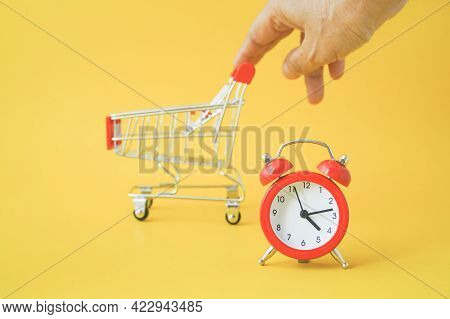 Red Analog Clock With Blurred Human's Hand And Shopping Cart On Yellow Background , Sale Promotion,