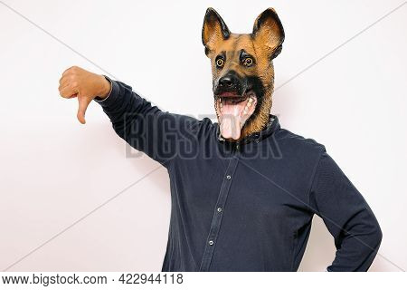 Person Disguised In A Dog Mask With Thumb Down As A Sign Of Disapproval On White Background, Concept