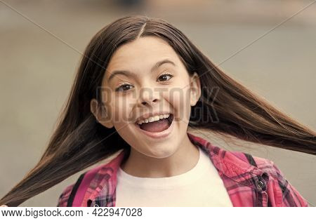 Because We Obsess About Your Hair. Happy Girl Hold Silky Long Hair Outdoors. Beauty Look Of Little C
