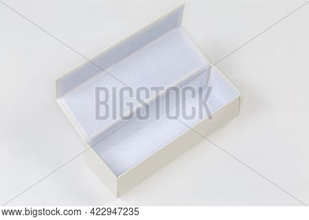 Open Empty White Rectangular Hard Spectacle-case With Magnet Closure On A White Surface