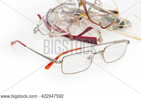 New Modern Classic Eyeglasses For Men In Metal Rim Against A Pile Of Old Broken Glasses On A White S