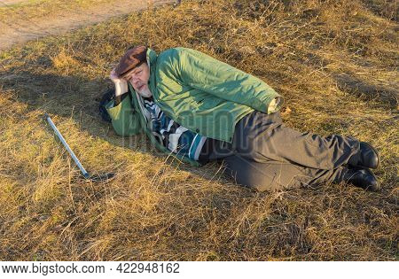 Caucasian Senior Hiker Has Short Rest Lying On The Roadside At Autumnal Evening