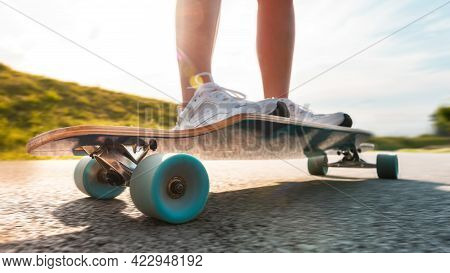 Wide Angle Longboard In Motion At Sunny Day On The Asphalt Road. Close Up Of A Spinning Wheel.