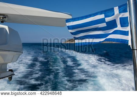 Greek Flag On The Background Of The Deep Blue Of The Aegean Sea Near Poros Island In Greece.