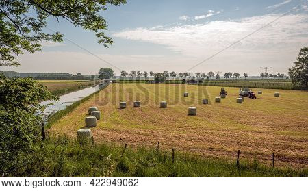 Hay Bales In Plastic Foil On The Freshly Mowed Grass. The Photo Was Taken On A Sunny Day In Springti
