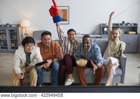 Multi-ethnic Group Of Sports Fans Watching Game Match At Home And Cheering Joyfully Raising Hands ,