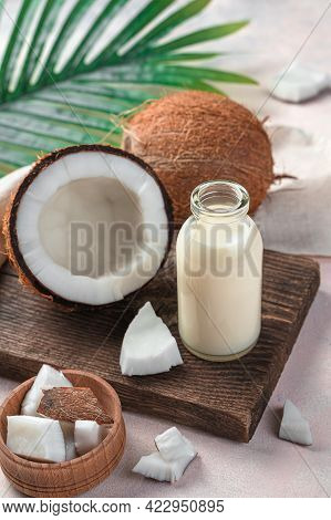 Coconut Milk, A Healthy Drink Made From Coconut On A Light Pink Background With Palm Leaves And Coco