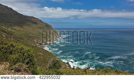 There Is Sparse Vegetation On The Slopes Of The Coastal Mountains. The Turquoise Waves Of The Ocean