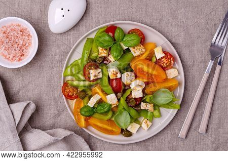 Salad Of Fresh Vegetables. Yellow And Red Tomatoes, Green Peppers, Capers, Basil And Feta Cheese Wit