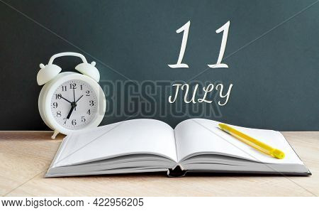 July 11. 11-th Day Of The Month, Calendar Date.a White Alarm Clock, An Open Notebook With Blank Page