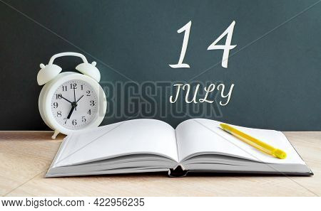 July 14. 14-th Day Of The Month, Calendar Date.a White Alarm Clock, An Open Notebook With Blank Page