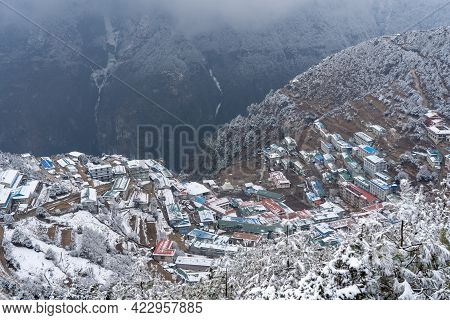 The Snow Covered Town Of Namche Bazaar Int He Valley Between The Mountains.