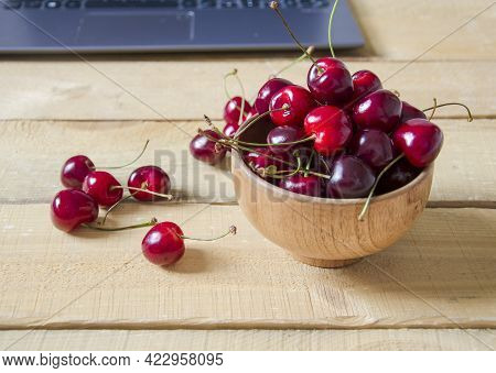 Red Berries In A Wooden Bowl. The Cherries Are On A Wooden Table, Behind A Laptop. Fruits Lie On A W