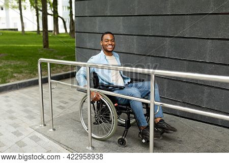 Happy Impaired Black Man In Wheelchair Entering Building On Ramp Outdoors, Full Length. Handicapped-