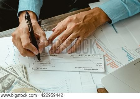 Businessman Hands Writing And Signing Cheque. Business, Finances And Money Concept