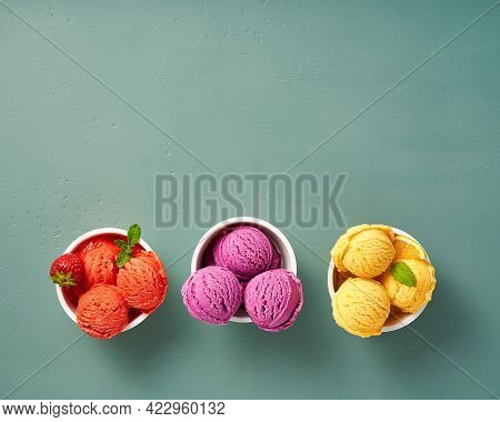 Gourmet Flavours Of Italian Ice Cream In Vibrant Colors Served In Individual Paper Cups On Blue Back