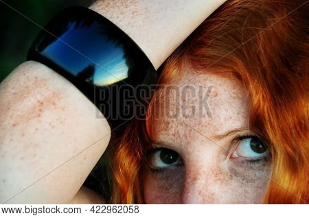 Portrait Of A Beautiful Freckled Redhead Woman With Black Bracelet With Reflection