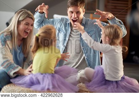 A young happy family making monster grimaces while playing in a cheerful atmosphere at home together. Family, together, playtime, home