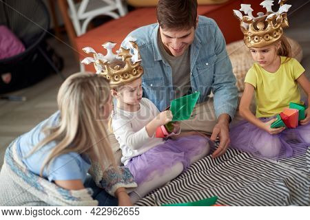 Little daugthers playing with paper boats while spending a playtime with their parents in a relaxed atmosphere at home. Family, together, love, home