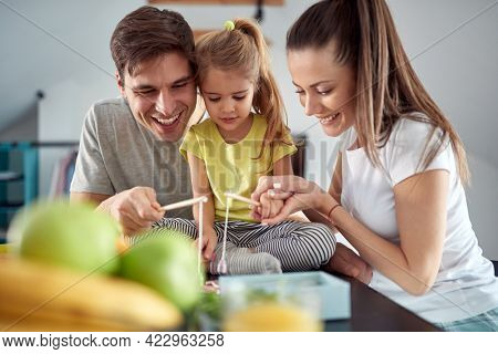 A young family playing at the table on a beautiful morning in the kitchen. Family, together, breakfast, home