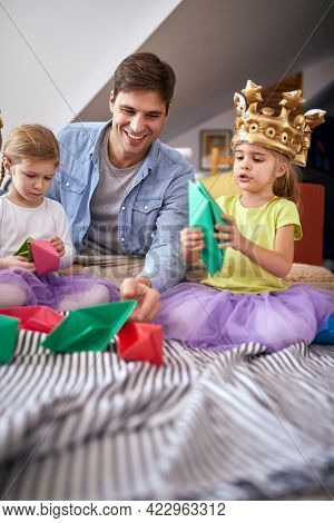 Little daughters sitting on the floor in a cheerful atmosphere at home with their father and playing with paper boats. Family, together, playtime, home