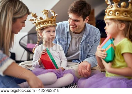 Little daughters are sulking while playing with their parents in a family atmosphere at home. Family, together, playtime, home