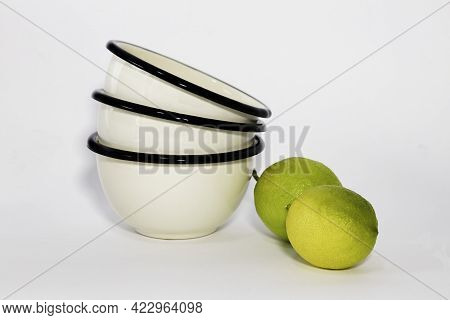 White Enamel Cups And Lemons Closeup On White Background