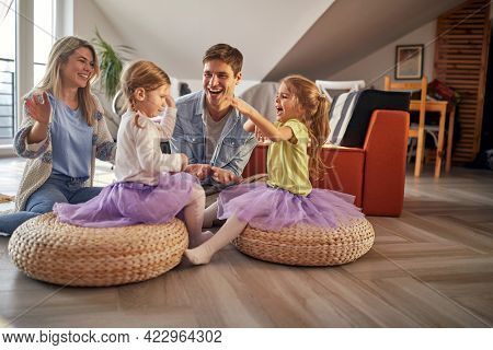 A young family sitting on the floor and having a good time in a cheerful atmosphere at home together. Family, together, playtime, home